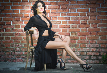 Charming brunette woman in black in front of red brick wall