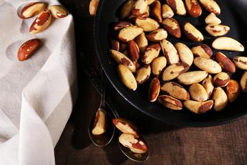 Tasty brasil nuts in pan on wooden background