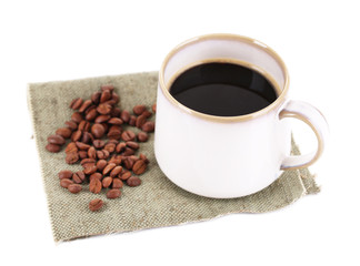 Cup with hot coffee and roasted coffee grains