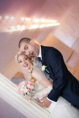 groom and the bride with a wedding bouquet stand near a  column