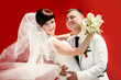 Happy groom and the bride on a red background