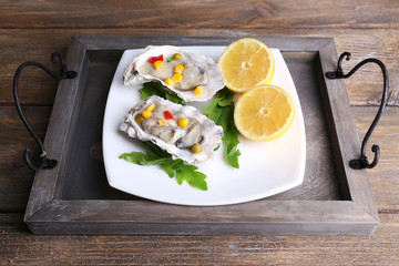 Tasty cooked oysters in shell on wooden table