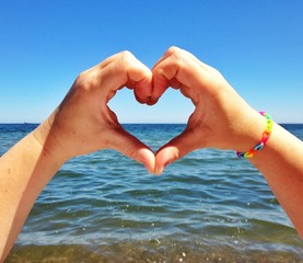 hands heart shape against the sea