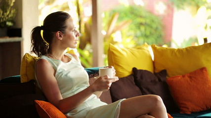 Beautiful businesswoman drinking tea, relaxing on sofa at home