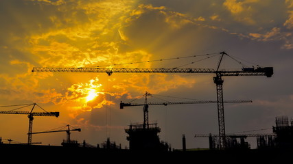 time lapse sunset and silhouette crane working in construction
