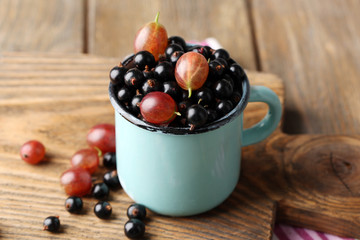 Ripe blackcurrants and gooseberries in mug