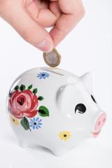 Münze in Sparschwein einwerfen