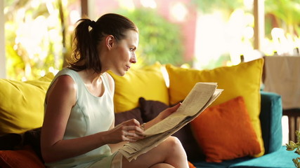 Businesswoman reading newspaper, eating snack on sofa at home