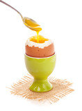 Light boiled egg in egg cup isolated on white