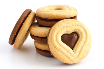 Stack of mixed white and dark biscuits with heart shape cut out.