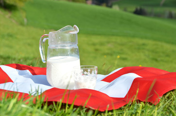 Jug of milk on the Swiss flag. Emmental, Switzerland