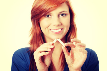 Young happy woman breaking cigarette