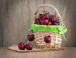 Cherries in a basket on wooden table