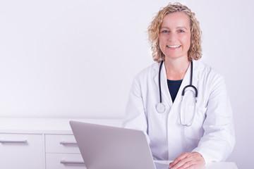 Freundliche Ärztin mit Computer