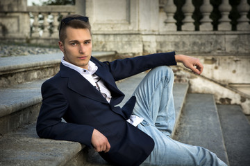 Attractive blond young man sitting on stone stair steps outside