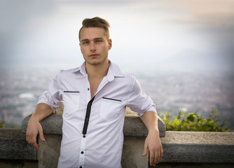 Blond young man on top of hill above Turin, Italy