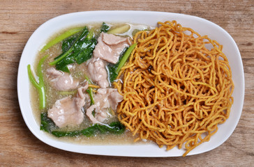 Noodle with pork and kale topping served in white bowl