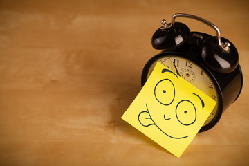 Post-it note with smiley face sticked on a clock