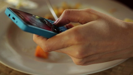 Close up of woman hand texting on smartphone and eating meal