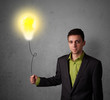 Businessman holding a lightbulb balloon