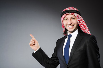 Arab businessman pressing virtual buttons against grey backgroun