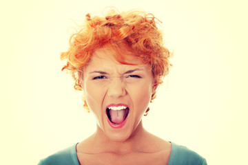 Furiouse young redhead woman screaming.