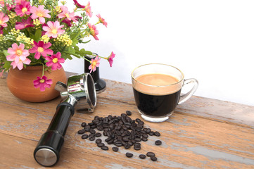 Hot coffee and coffee beans with flower clay pot.