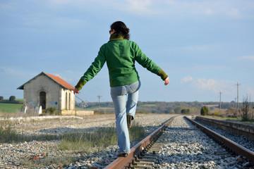 mujer haciendo equilibria en las vias del tren