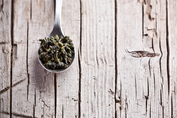 spoon with dried green tea leaves