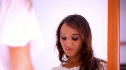 Beautiful young girl paints lips, eyelashes, powder, preens near