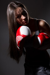 Girl with boxing gloves in front, bowed her head.
