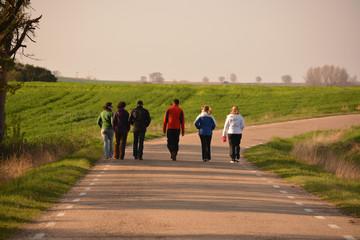 grupo de seis personas caminando por una carretera