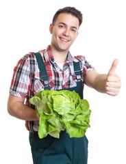 Junger Gärtner mit Salat freut sich