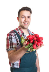 Junger Gärtner mit Radieschen in der Hand
