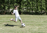 Fototapety Child playing football in a stadium