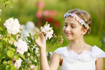Rose garden - beautiful girl playing in the garden