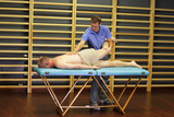manual therapist working with  man's leg and back