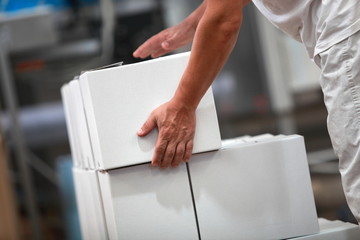 Manual worker working with boxes in factory