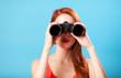 Leinwanddruck Bild - Redhead girl with binocular on blue background.