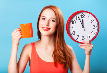 Redhead girl with tea cup and huge clock on blue background.