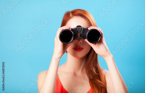 Leinwanddruck Bild Redhead girl with binocular on blue background.