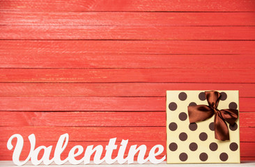 Wooden word Valentine and gift on wooden table.