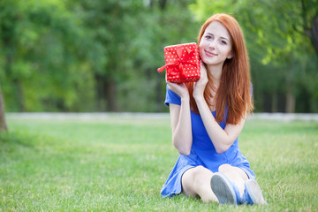Redhead women with gift at green grass.
