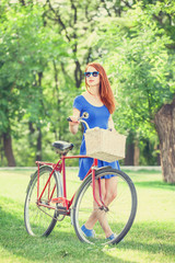 Redhead with bicycle in the park.