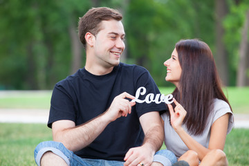 Teen couple with word Love in the park