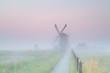 Dutch farmland with windmill in fog