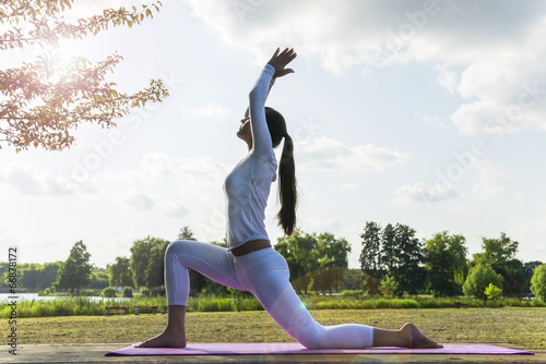 canvas print picture Pretty woman doing yoga exercises in the park.
