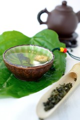 Cup of healthy tea on a green leaf