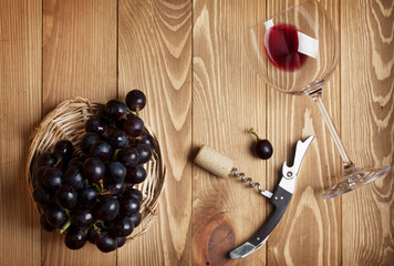 Red wine glass, corkscrew and grape