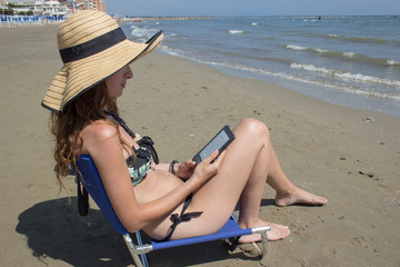 girl reading ebook on the beach
